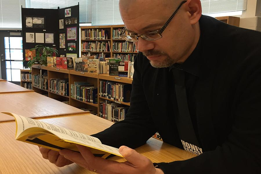 Librarian Bradley Walton reads a book in the library.