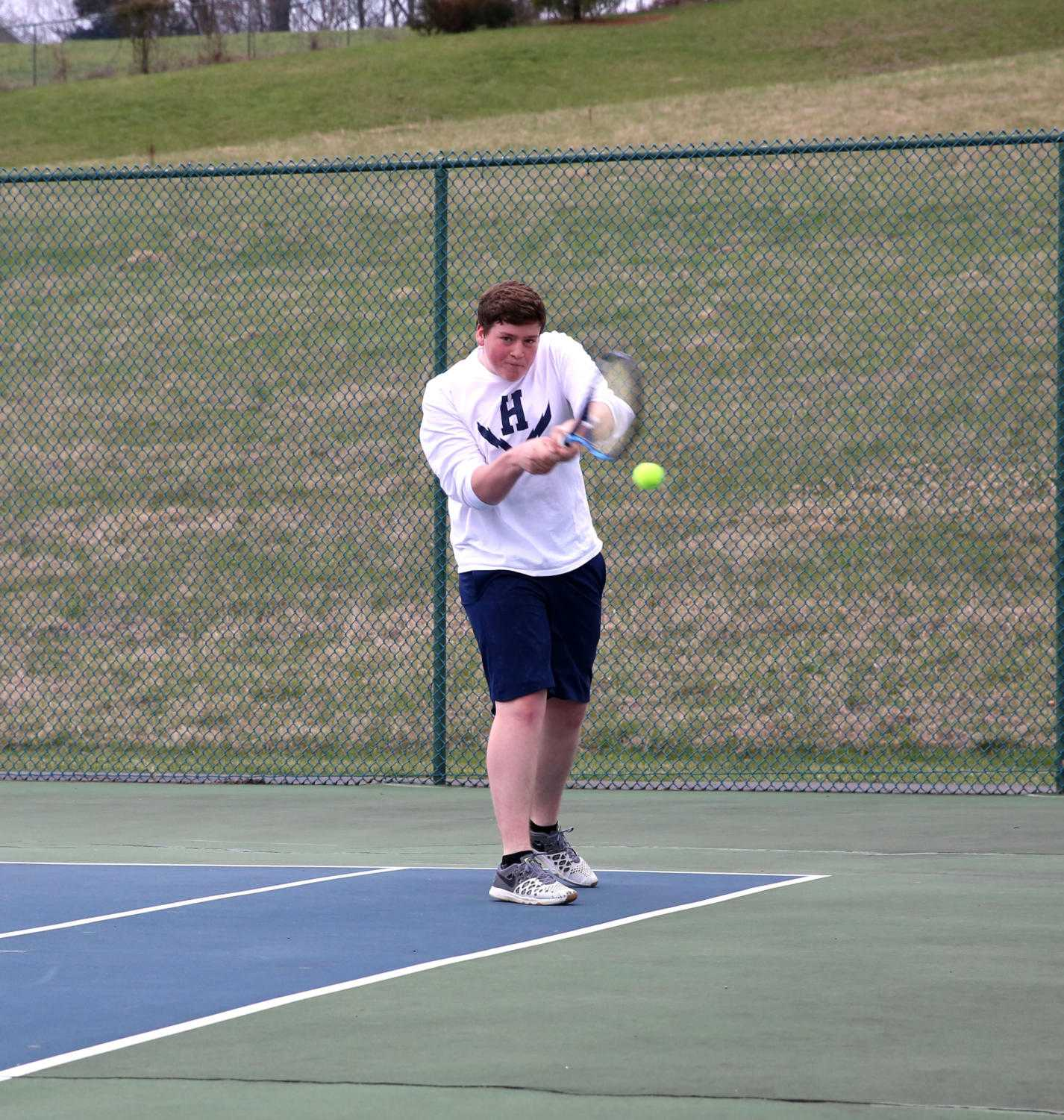 Junior Tobias Yoder steps up and returns a low shot from Turner Ashby's Canon Secord during his doubles match.