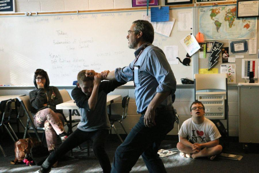 Musical director and drama teacher Stan Swartz exemplifies proper stage combat to his drama class with freshman Kai Johnson.