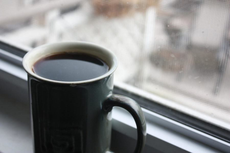 A+cup+of+coffee+sits+in+a+windowsill+